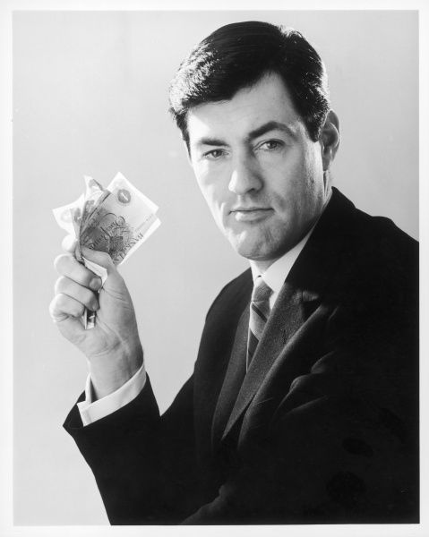 A dashing man clutches a fistful of pound notes