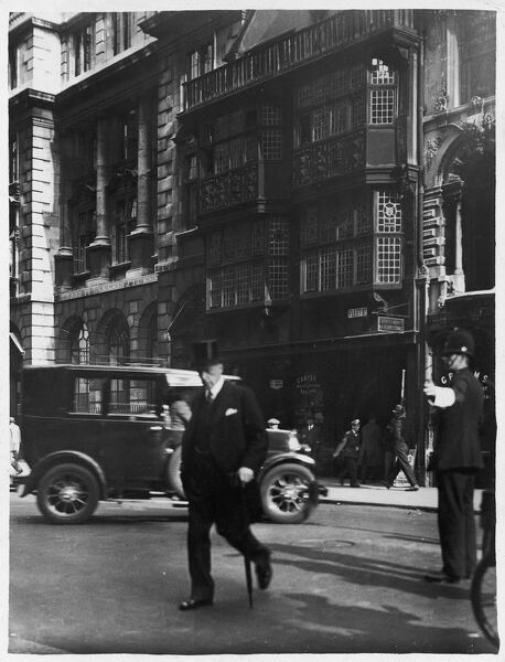 A rich gentleman crosses Fleet Street outside Prince Henry's Room, one of the few timber- framed buildings (dating from the 1600s) still in existence in London