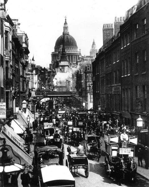 Photograph showing the view east along Fleet Street, towards Ludgate and St. Paul's Cathedral, c.1894. A large number of horse-drawn carriages can be seen rushing along the street as a steam train heads south towards Blackfriars
