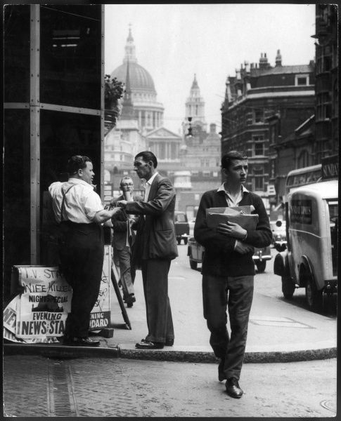 Fleet Street in London: a man buys a paper from a news stand; St Paul's Cathedral is visible in the distance