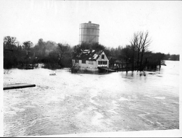 Flood water from the river Thames at Staines in Surrey, threatens the premises of W S Biffen Boat Builder and the gasometer, one of the largest in the world