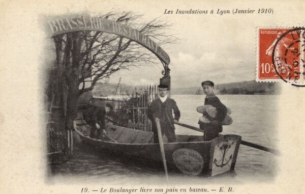 Flooding in Lyon in January 1910 caused a great rise in the water level of the River Rhone. Here a baker and his boys in his traditional bateau boat, delivers bread to a Brasserie restaurant cut off by all other routes of transportation Date: 1910