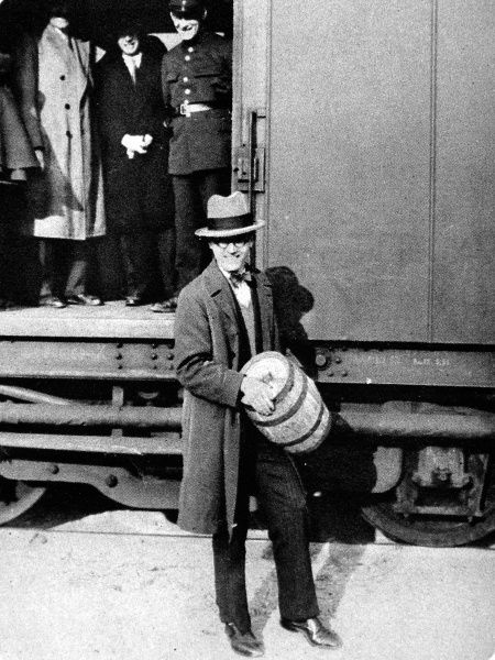 Photograph of man holding keg containing gold worth 1,500,000 francs, as the gold arrives in France