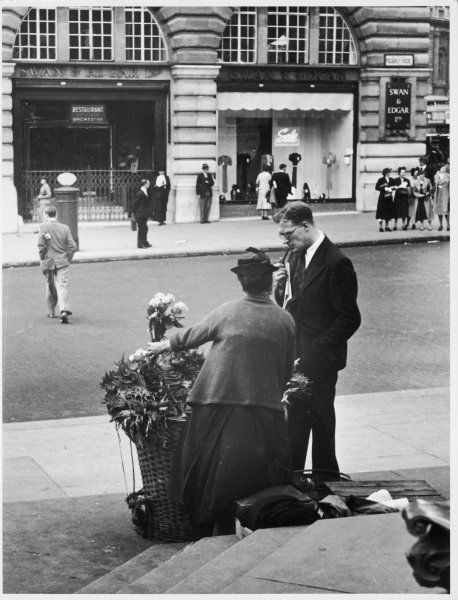A lady sells flowers to a gentleman in a London road 2