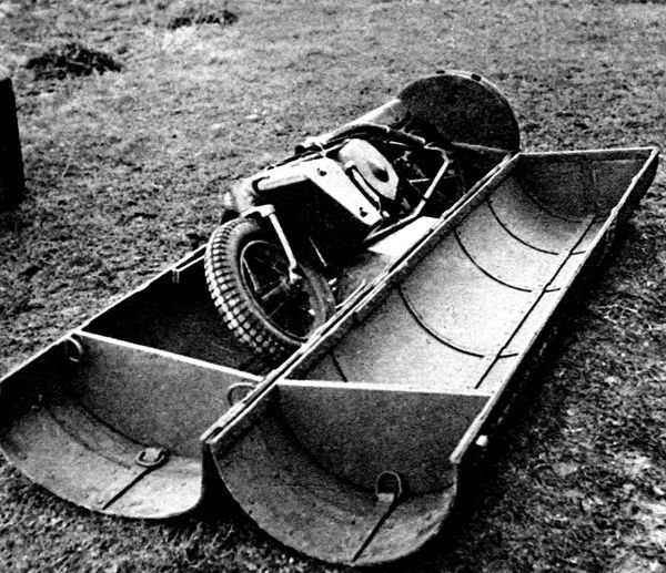 Photograph showing a folding motorcycle, in its parachute container, used by the British Airborne forces, 1944. Equipment such as this was used in Operation 'Market Garden' by the British First Airborne Division at Arnhem in Holland