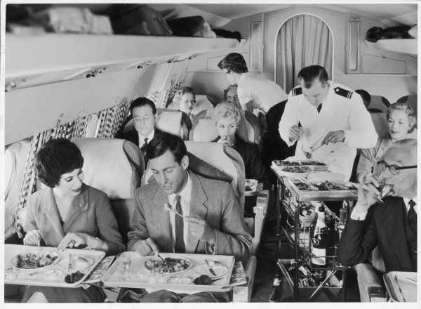 An Airline Steward and Air Hostess serve a roast meal to flight passengers