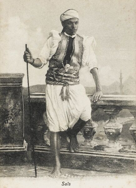 A Footman from Sais, Egypt (on the Western Nile), wearing a fine patterned waistcoat / jerkin and holding a long thin stick