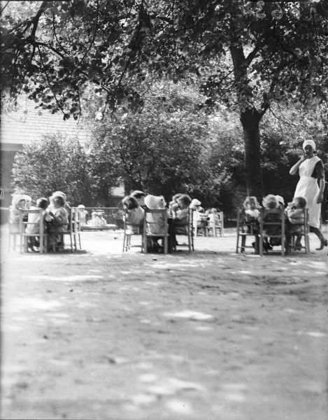 Children eating on tables in the sunshine at the Foundling Hospital, grounds, Guildford Street, London
