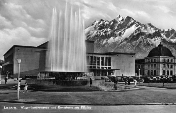 The fountain and the concert hall, with the Pilatus mountain in the background, at Lucerne, Switzerland. Date: circa 1940