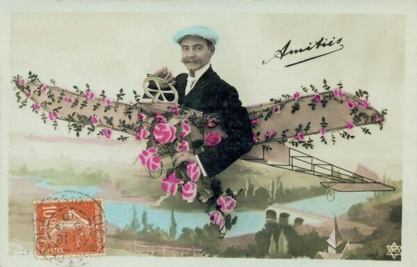 A French aviator on a greetings postcard, his aeroplane decorated with lots of pink flowers as he flies above a French town. Date: early 20th century