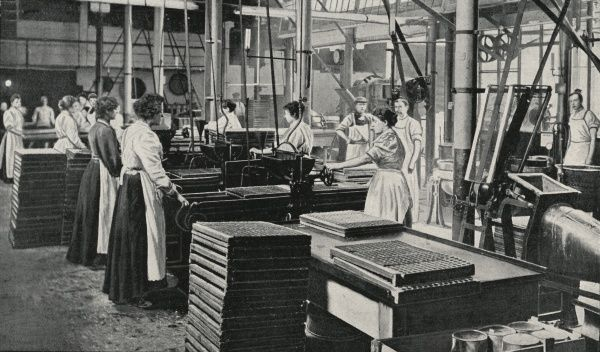 Women handle large wooden trays in the French Cream room at the sweet manufacturers Clarke, Nickolls and Coombs, at Hackney Wick, London. The firm made 'Clarincos' chocolates