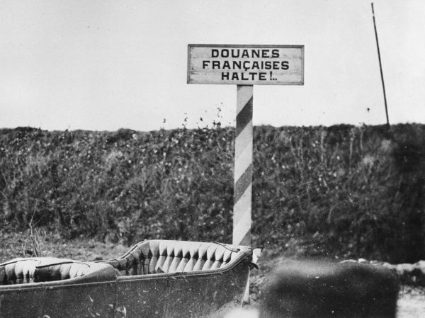 A French customs sign (possibly a joke) at the side of the road on the Western Front during the First World War. With an empty open-topped car at the side. Date: 1914-1918