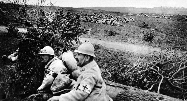 French infantry in the front line on hands and knees creeping forward to within charging distance. Two soldiers are seen in the foreground wearing steel helmets