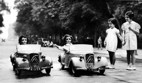 Photograph showing two model cars offered 'by the children of France' to Princess Elizabeth and Princess Margaret, pictured with two dolls 'Marianne' and 'France' sitting in them and two young French girls looking on, 1938