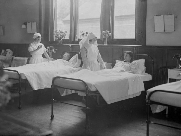 A matron and a nurse attending to bedridden patients in one of the wards of the Marie Curie Hospital, Paris, France. Date: early 1930s