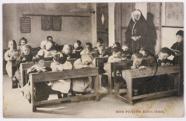 Very young children in a church school, watched over by their teacher, a nun : note the boards hanging on the wall, teaching the alphabet and grammar