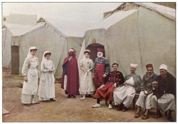 Nurses of the French Red Cross, posing for a photograph with their patients, otside one of their tents at Casablanca, Morocco