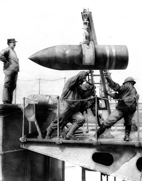 Photograph of a sixteen-inch shell being hoisted into position by French soldiers for loading into its gun. The caption described the weapon as 'the modern lord of battle.&#39