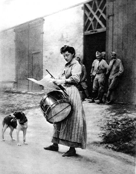 A photograph of a French woman employed as a 'garde champtre,' during the First World War. She is shown performing part of her duties, the reading of an official proclamation in a French village&quot