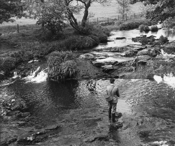 What could be more relaxing than a spot of angling in a country stream? Date: circa 1960