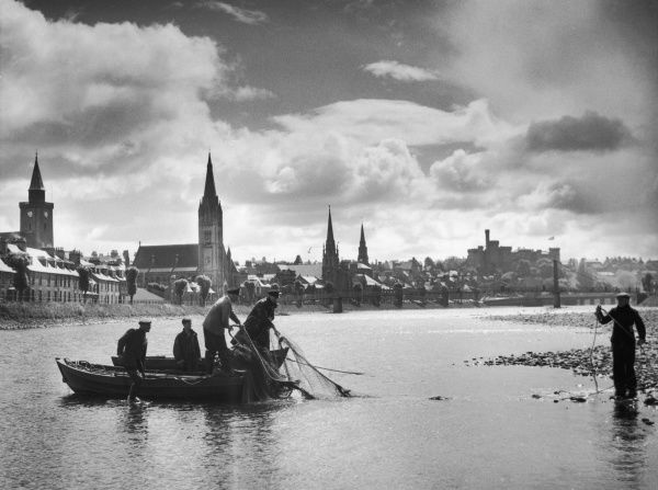 Scottish salmon fishermen fishing in the Friars Shot Pool of the River Ness. In the background is the town of Inverness with its castle, Inverness-shire, Scotland