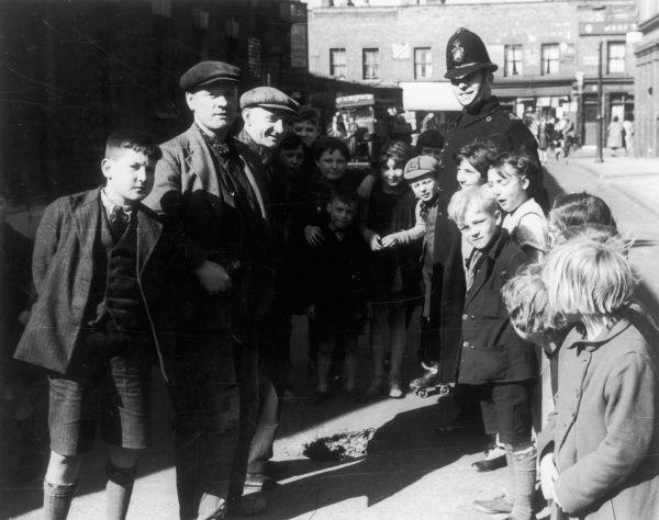 A friendly London 'Bobby', standing around a hole in the road with a group of children and Working Class men in flat caps