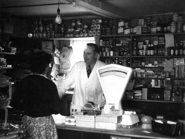 A friendly village shop in Colebourne, a village in the Cotswolds, Gloucestershire, England. Date: 1953