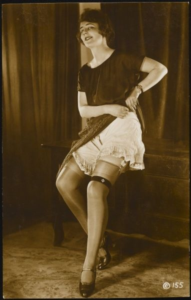 A young woman lifts her dress to reveal a lace edged pair of camiknickers (French knickers or 'step-ins')revealing a glimpse of her stocking tops, suspender belt and garter