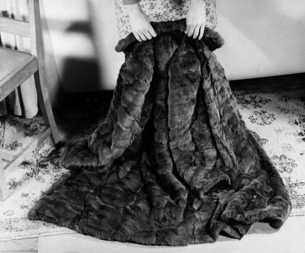 A luxurious fur coat, spread out over a carpet to demonstrate its seams and sleeves. Date: 1940s