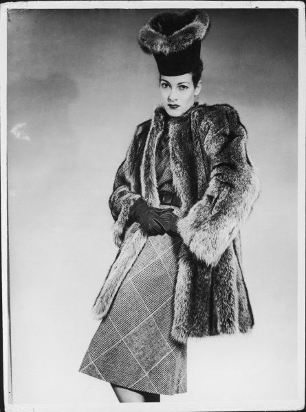 A diagonal plaid / check dress worn with a 3/4 length coat in grey fur & a tall, brimless hat with a flared crown trimmed in the same fur