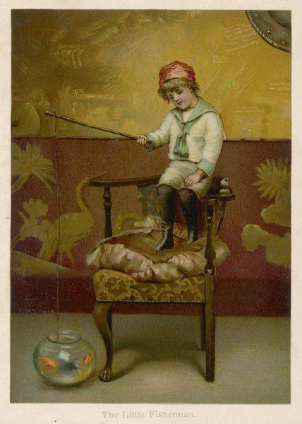 A little boy stands on a chair and 'fishes' in a goldfish bowl