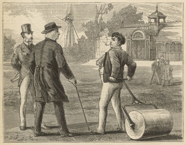 A gardener, smoking a pipe and tending a school cricket field, stops to talk to two smartly dressed gentlemen