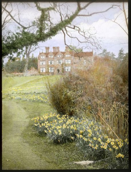 View of the gardens at Gravetye Manor, near East Grinstead, West Sussex, showing daffodils growing in the foreground, and the Elizabethan manor house in the background