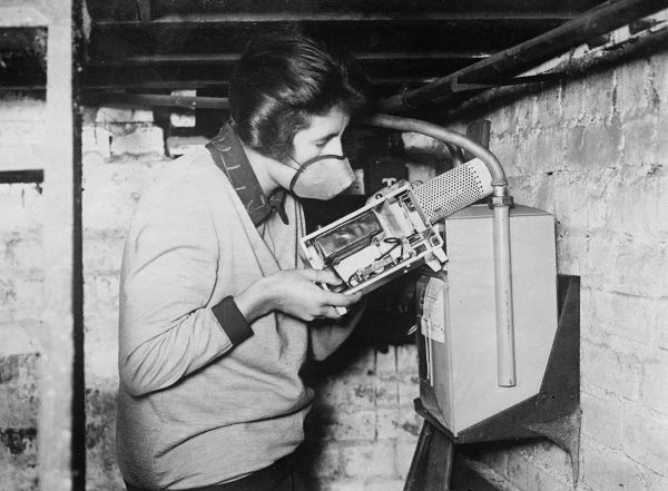 A young woman demonstrates how to use a new device for detecting gas leaks. Date: early 1930s