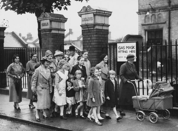 Mothers leave an Ilford school with their children after a gas mask fitting