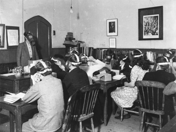 Students wearing gas masks while studying during World War II