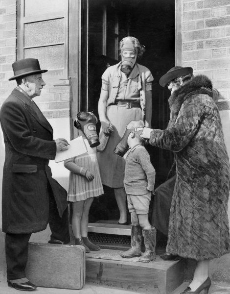 Two wardens for the Air Raid Precaution Scheme fitting children with gas masks during a house to house visit in Beckenham, Kent