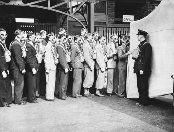 Group of men queuing to register, probably for the ARP, wearing gas masks during World War II