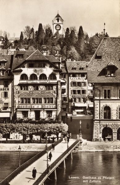 View of the decorated facade of the Gasthaus zu Pfistern, on Lake Lucerne, Switzerland, seen from across the water. On the horizon is the Zytturm, or clock tower. Date: 1940s