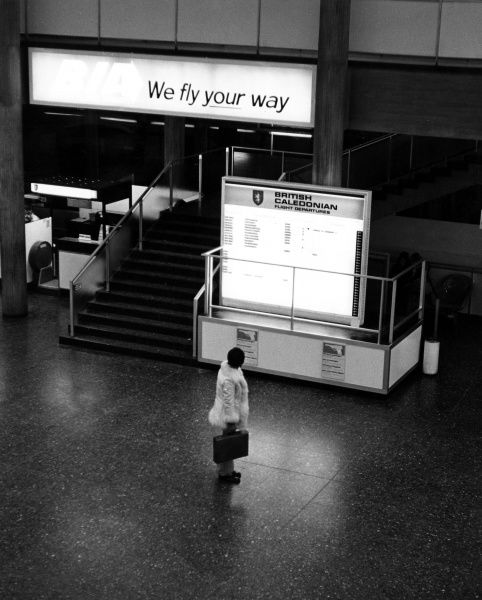 A passenger stands alone in the airport checking the flight departures for British Caledonian Date: late 1960s