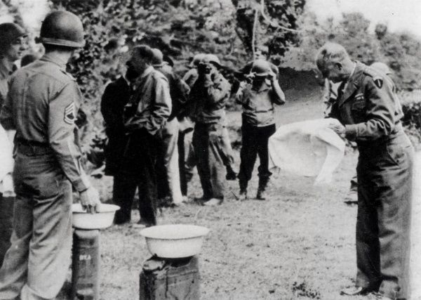 Photograph of General Dwight Eisenhower washing his hands during his visit to the Normandy Beach Head