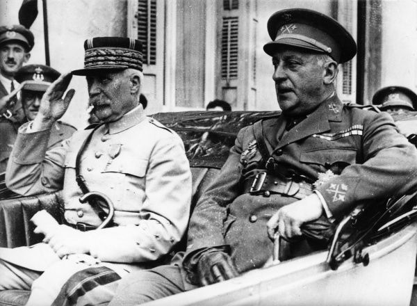 General Philippe Petain (1856-1951), French army officer, seen here (left) saluting from the back of a car. A British officer sits next to him. Date: circa 1914-1918