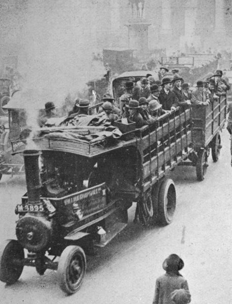 Londoners travelling by a steam-wagon and trailer combination past the Royal Exchange in the City of London during the General Strike