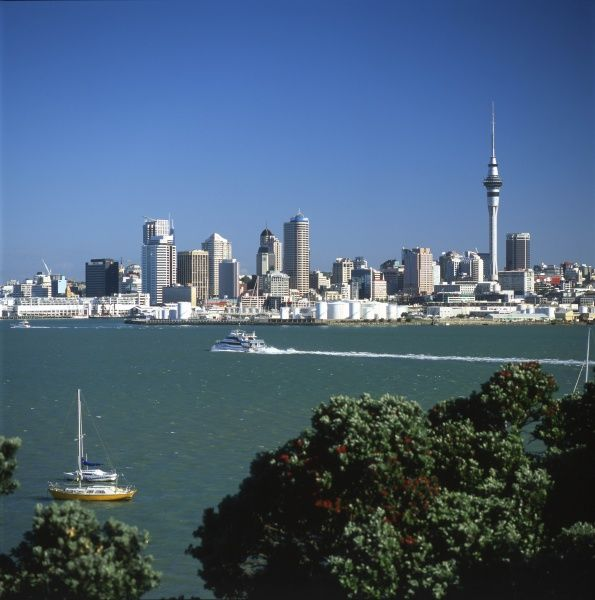 A general view of the central business district of Auckland, North Island, New Zealand, with a boat travelling across the harbour
