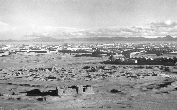 General view of the Iranian desert, with a few buildings, and mountains in the background