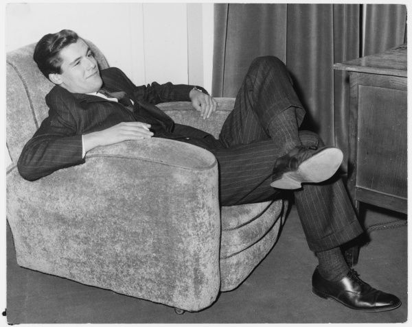 A young gentleman in a pin- striped suit relaxes in a comfortable armchair
