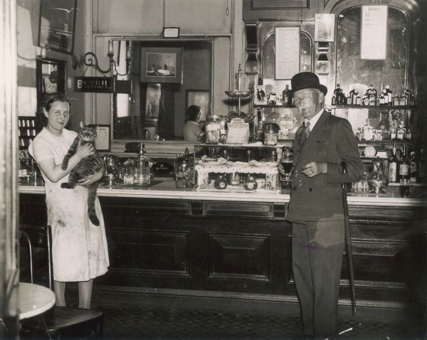 A well-dressed old businessman in a suit having a pint at the Sloane Square underground station pub. The barmaid holds the pub cat in her arms