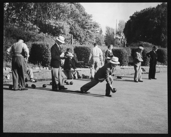 Older gentlemen (and one lady) enjoying a leisurely game of bowls on an English bowling green