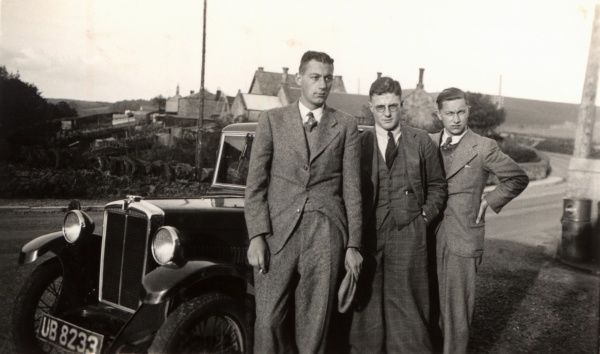 Three smart Gents stand beside a Morris 8 Saloon - the first of the 'Minor' series