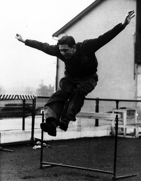 Geoffrey Dyson OBE, chief coach for Britain in track and field from 1947 to 1961, seen leaping over a hurdle